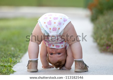 One-year baby girl playing upside down on the street #113182546