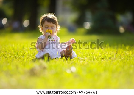 One year little girl sniffing flower summer park outdoors
