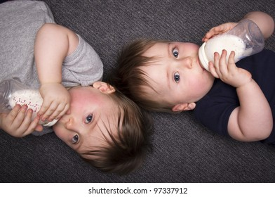 A stock photo of one year old twin boys lying on the ground drinking from bottles