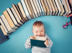 One year old baby among books with spectackles.Happy little child reading