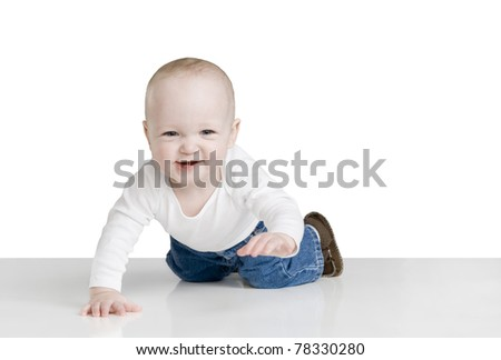 one year old baby boy crawling toward the camera, on shiny white surface, great smile with two bottom teeth showing