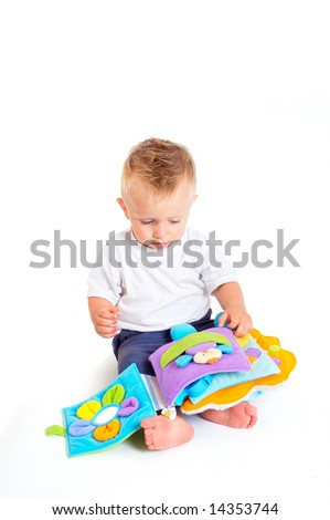 One year old baby boy enjoys playing with toys. Studio Shot. All toys visible on the photo are officially property released.