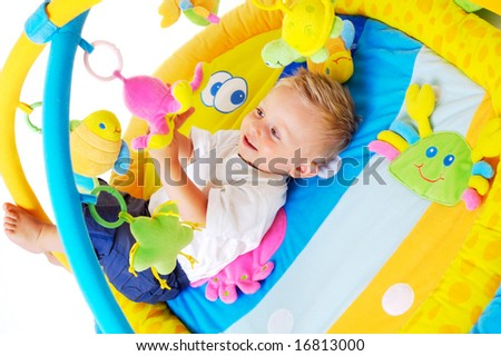 One year old baby boy enjoys playing with toys. Studio Shot. All toys visible on the photo are officialy property released.