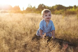 One-year-old baby boy sitting alone in a field, making funny faces.