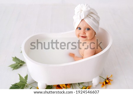 One year old baby girl takes bath. In blue swimming cap. Bathroom. The girl bathes in a basin. Clothes are dried on a hanger. Bath screens.