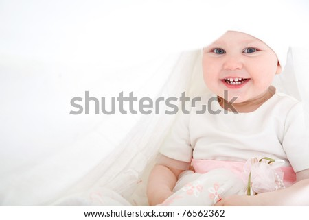 One year old baby girl wearing white and pink dress sitting in a white