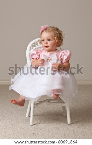 One year old baby girl wearing white and pink dress sitting in a white wicker chair.