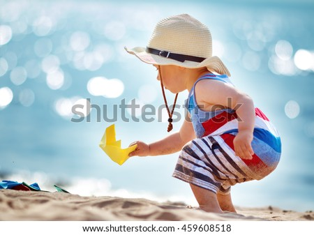 one year old boy playing at the beach in straw hat. Child with a paper ship at sea #459608518