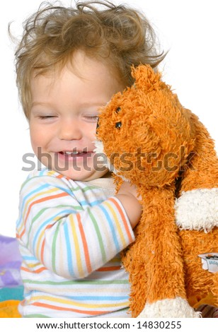 stock photo : one year old boy with curly hair is hugging his ginger cat;