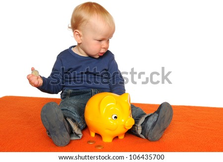 One year old boy with yellow piggy bank