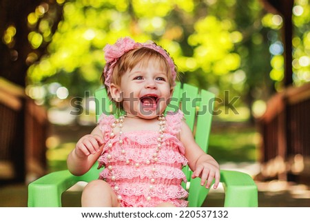 One year old girl playing outside in a pink romper -- image taken at San Rafael park in Reno, Nevada