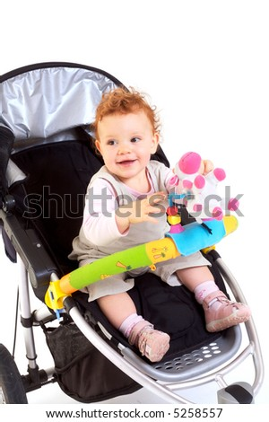 One year old red haired baby girl with baby stroller. Studio Shot. All toys visible on the photo are officially property released.