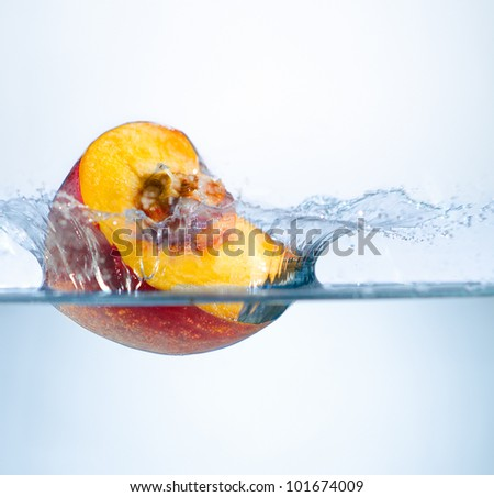 one yellow peach big  strawberry  drop in blue water with splashes