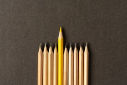 One yellow pencil standing out from the series of gray pencils. On grey background. Sign symbol idea concept of leadership, divergent, diversity. Standoff of the individual to society.