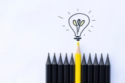 one yellow pencil with a light bulb among black ones. business concept