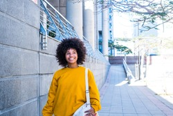 one young and beautiful businesswoman walking after working day in the office. Cheerful African or American girl