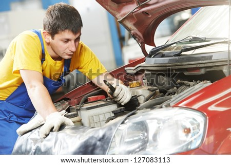 One young auto mechanic examining sparking plug during automobile car maintenance at engine repair service station