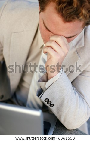 One young businessman with head in hands leaning over laptop