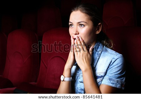 One young girl watching movie in cinema