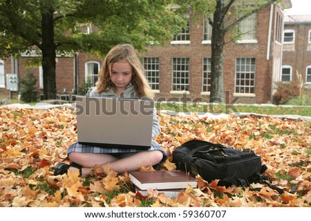 one young grade school student studying outdoors on a laptop in autumn