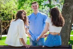 One young guy talking to two girlfriends in a summer park