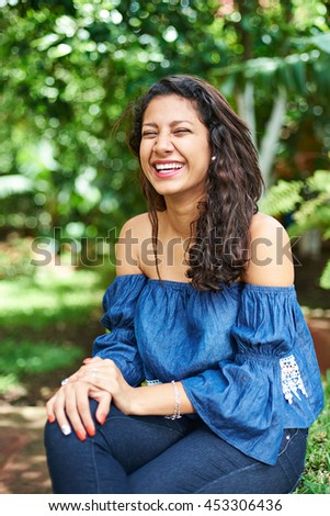 one young latino girl laughing in park #453306436