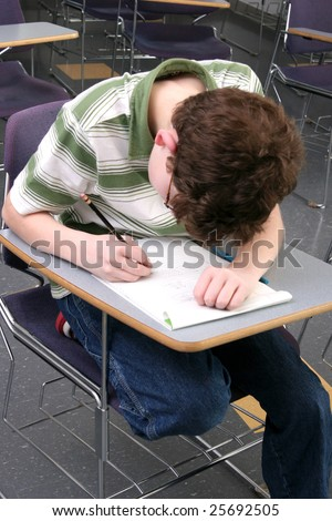 one young male student studying in class reading and writing