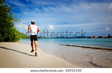 One young man running on a tropical empty beach at sunrise, rear view ; Seychelles, Indian ocean