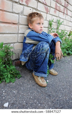 one young man sits against graffiti alone