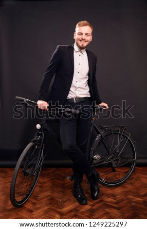 one young man smiling honestly, 20-29 years old, posing, leaning on on a bicycle inside studio. black seamless background behind him. real person, not a model.