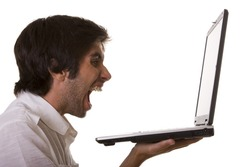 one young men screaming with his computer (isolated on white)