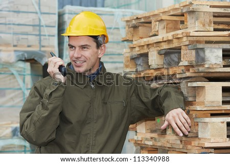 One young smiling warehouse manager worker speaking on radio transmitter near wood pallet