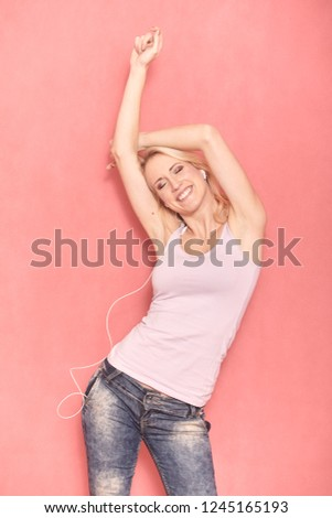 one young smiling woman enjoying music, while listening to it on her earbuds, arms raised swining hips and dancing 20-29 years old, long blond hair. Shot in studio on pink background.