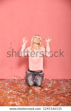 one young smiling woman portrait, looking to camera, kneeling on floor surrounded with falling confetti, 20-29 years old, long blond hair. Shot in studio on pink background.