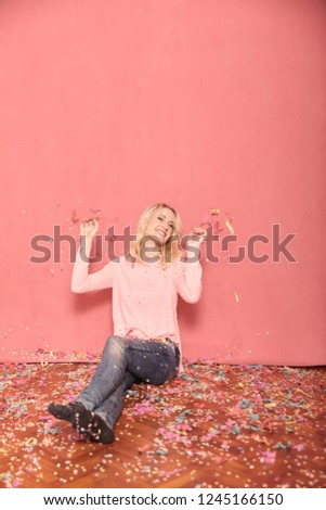 one young smiling woman portrait, looking to camera, sitting on floor surrounded with falling confetti, 20-29 years old, long blond hair. Shot in studio on pink background.