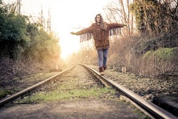 One young woman balancing on rail - Pretty girl walking on rail in search for adrenaline