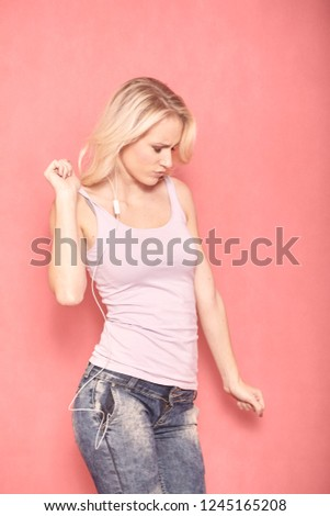 one young woman dancing to music, listening on earphones, truly enjoying it with her eyes closed, and arm raised up, 20-29 years old, long blond hair. Shot in studio on pink background.