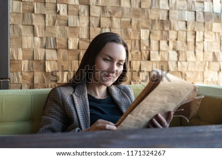 One young woman sitting in a restaurant with a menu in her hands makes a choice of dishes.