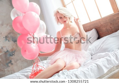 One young woman sitting on the bed wearing bra and sexy skirt holding balloons touching curl looking camera smiling playful