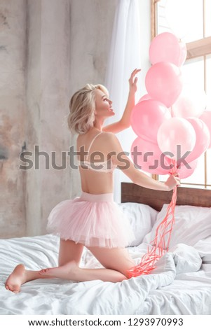 One young woman standing on the bed wearing bra and sexy skirt playing with balloons smiling happy