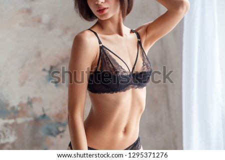 One young woman standing wearing lingerie body close-up looking aside sensual