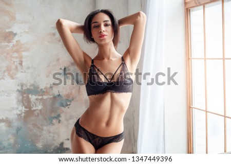 One young woman standing wearing lingerie hands behind head posing to camera sensual