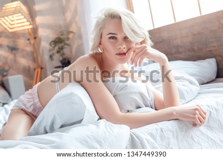 One young woman wearing pajamas lying on bed holding pillow looking camera sensual close-up