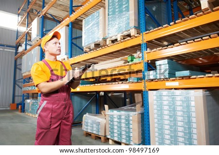 one young worker inspector man in uniform in front of warehouse rack arrangement stillages