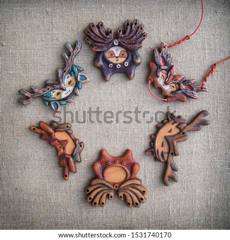 Ongons. Unusual handmade jewelry. Traditional wooden decorations and the process of creating them. Decorations in folk style in the form of fantastic animals.