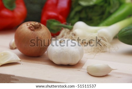 Onion and garlic on a wooden chopping board.