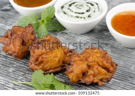 Onion Bhajis & Dips - Deep fried south asian snack with chili sauce, mint raita and mango chutney, garnished with mint and coriander leaves on a slate.