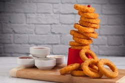 Onion rings and sauces in front of the white wall