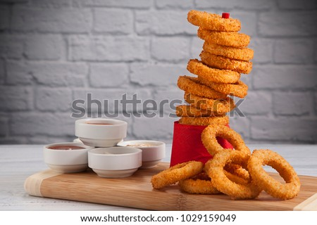 Onion rings and sauces in front of the white wall #1029159049