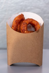 onion rings in a cardboard bag on a gray background.
